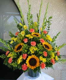 Sympathy basket of carnations, yellow chrysanthemus, sunflowers and yellow gladiolus.