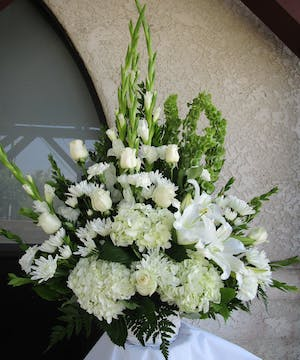 All-white flower arrangement in a basket for sympathy or funeral.