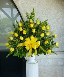 Two dozen roses with yellow solid aster in a white urn.
