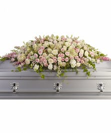 Casket spray of light pink and white flowers accented with greenery.
