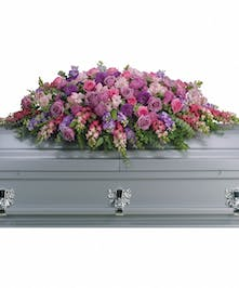 Casket spray of lavender and pink flowers accented with greenery.