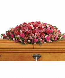 Casket spray of hot pink and light pink flowers accented with greenery.