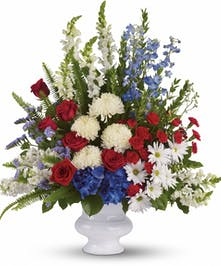 Red, white and blue patriotic flower arrangement in a white urn.