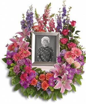 Cremation bouquet of purple, pink, lavender and peach flowers to surround an urn or photograph.