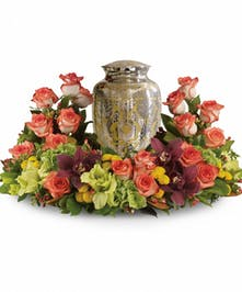 Cremation wreath of orange roses, cymbidium orchids, gladioli, and more to surround an urn or photograph.