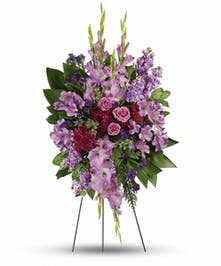 Lavender colored flowers and greenery in a spray funeral arrangement.