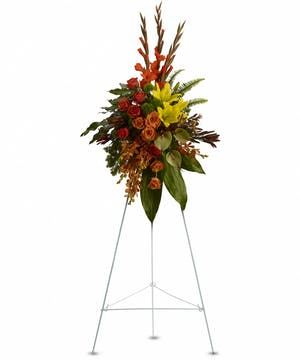 A breathtaking funeral spray using orange, red, and yellow flowers