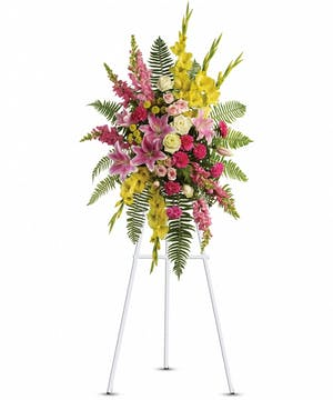 Sympathy spray of green and pink flowers with greenery presented on an easel.