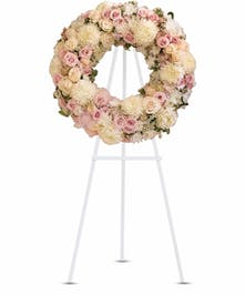 White and pink flowers arranged in a wreath on a standing easel.