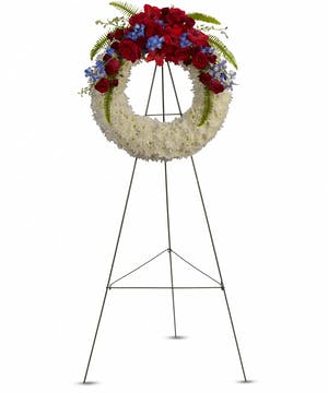 A lovely funeral wreath with patriotic colored flowers