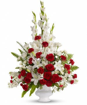 Sympathy tribute of white and red flowers presented in a white urn.