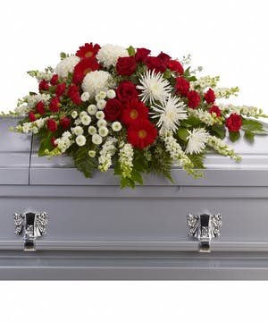Casket spray of red roses and gerberas, white chrysanthemums, larkspur and greenery.