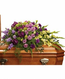 A lush casket spray with green, lavender, and purple flowers.