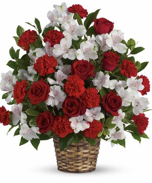 An impressive funeral basket including red and white flowers