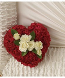 A sweet casket insert made of red carnations and white spray roses.