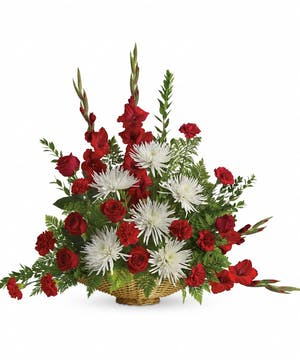 Sympathy basket of red roses and carnations, white spider chrysanthemums, and greenery.