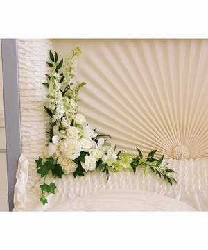 A magnificent casket insert with all white flowers