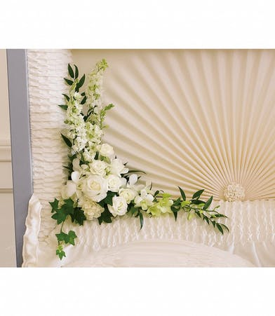 Casket insert of white orchids, roses, carnations and more.