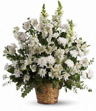 Funeral basket of all-white flowers including alstroemeria, snapdragons, stock and chrysanthemums.