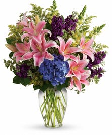 Blue hydrangea, pink oriental lilies, yellow snapdragons, purple stock and greenery in a clear glass vase.