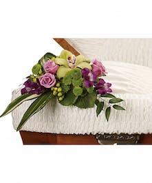 A radiant casket insert with green, lavender, and purple flowers