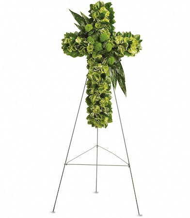 Sympathy cross of green flowers accented with greenery presented on an easel.