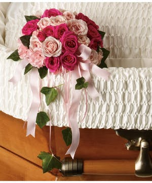 A delicate casket insert with hot pink and soft pink flowers