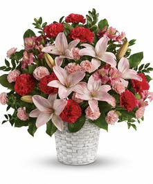 Sympathy basket of pink Asiatic lilies, alstroemeria, carnations and more with greenery.