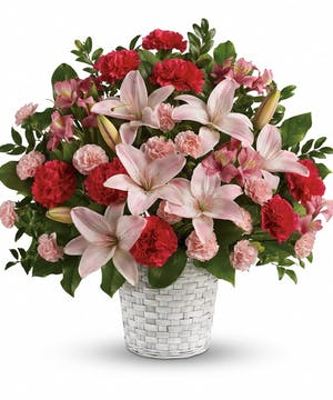 A stunning funeral basket using hot pink and light pink flowers