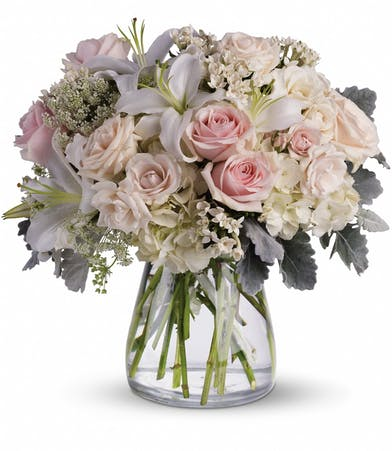 White, creme and light pink roses, lilies and Queen Anne's lace in a clear glass vase.