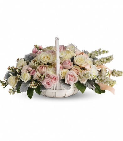 Sympathy basket of white and light pink roses, larkspur, mums and dusty miller.