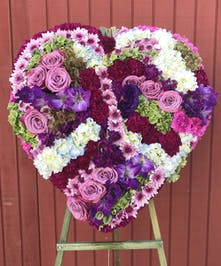 Sympathy heart of lavender, green, purple and blue flowers.