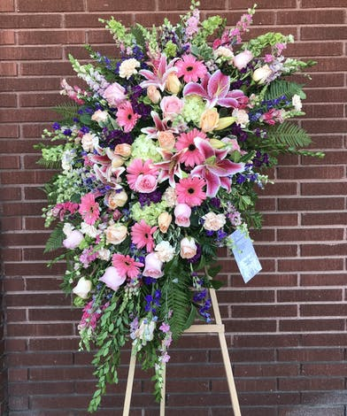 Sympathy spray of pink and green flowers presented on an easel.