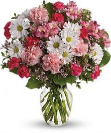 Pink alstroemeria and carnations, white daisy spray chrysanthemums and greenery in a clear glass vase.