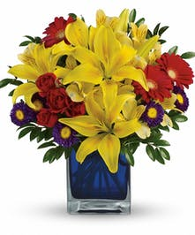 Yellow lilies and red flowers in a blue glass cube vase.
