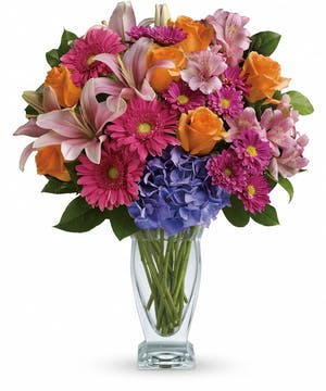 Pink lilies, orange roses, blue hydrangea, pink gerberas and alstroemeria, purple chrysanthemums and more in a clear glass vase.
