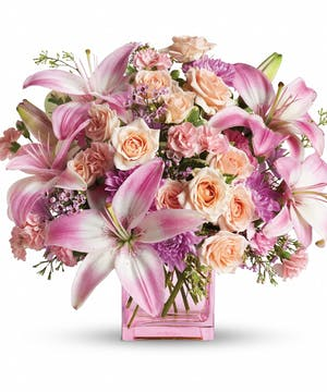 Variety of pink and peach flowers arranged in a pink glass cube vase.
