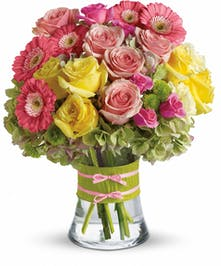 Pink roses and gerbera daisies, yellow roses, green button mums, green hydrangea, and greenery in a leaf-lined cube vase.
