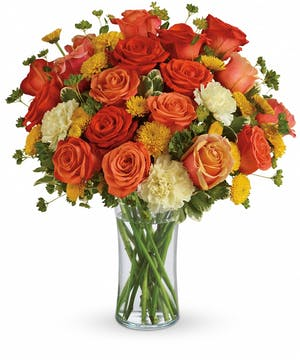 Yellow button mums, orange roses, and yellow carnations in a clear glass vase.