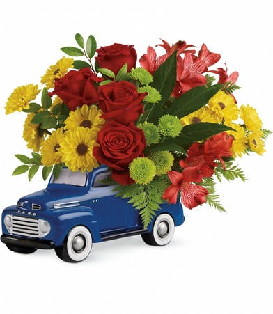 Ford pickup truck keepsake filled with bright red, yellow, green and orange flowers.
