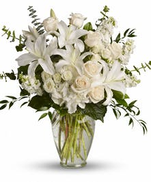 White hydrangea, spray roses and stock, peach roses and more in a tall glass vase