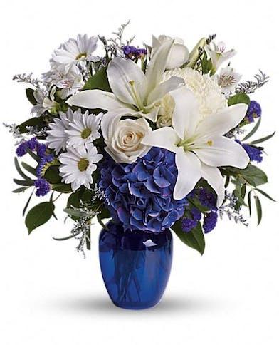 White flowers and dark blue hydrangea in a dark blue glass vase.