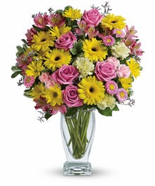 Yellow and pink flowers in a clear glass vase.