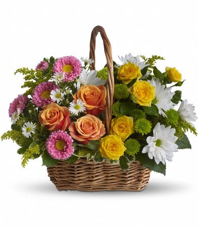 Wicker handbasket filled with orange and yellow roses, white daisy spray chrysathemums, green button spray chrysanthemums and more.