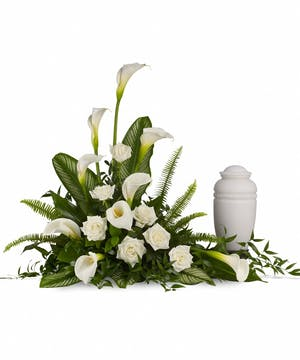 All-white sympathy arrangement of calla lilies, roses and greenery.