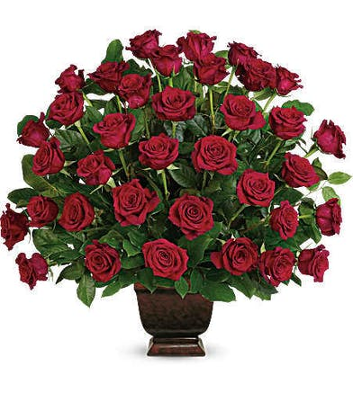 Sympathy arrangement of red roses and greenery.