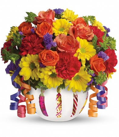 Orange roses, red carnations and yellow daisy spray chrysanthemums in a birthday themed vase with ribbon.