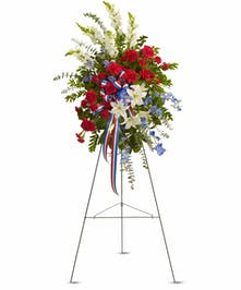 Patriotic easel spray of red, white and blue flowers.