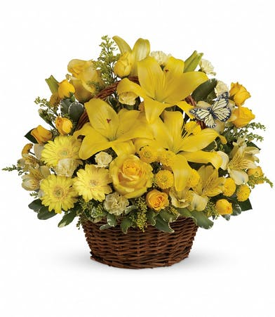 Yellow flower arrangement in a wicker basket.