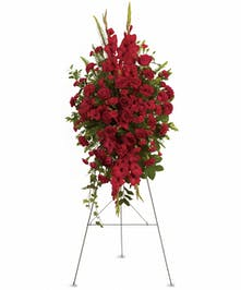 Sympathy spray of all red flowers and greenery displayed on an easel.
